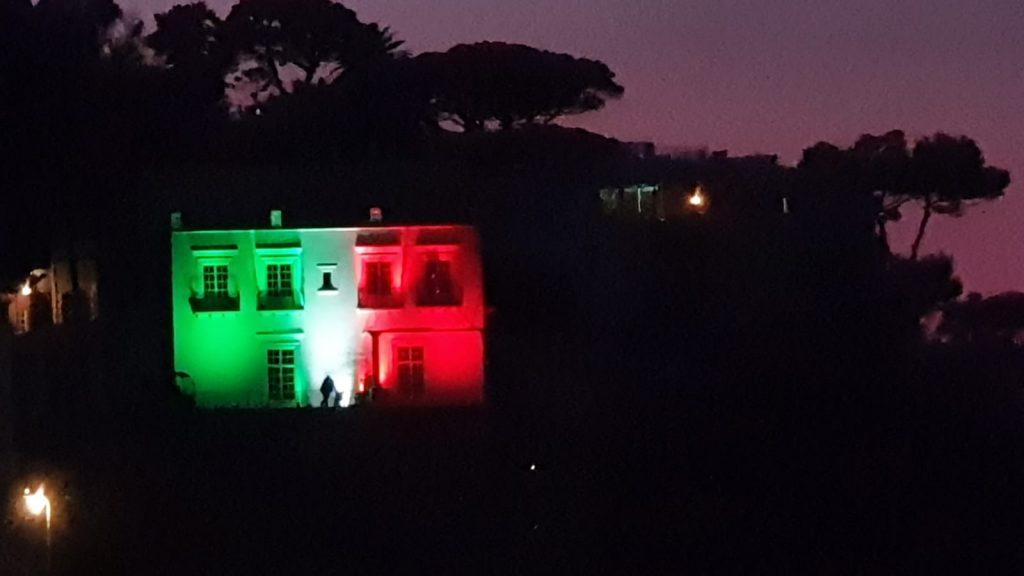 Un tricolore di speranza sulla facciata dell'hotel illumina la sera caprese. LE FOTO